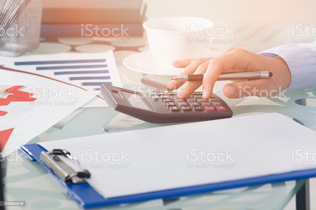 Businesswoman using calculator stock photo