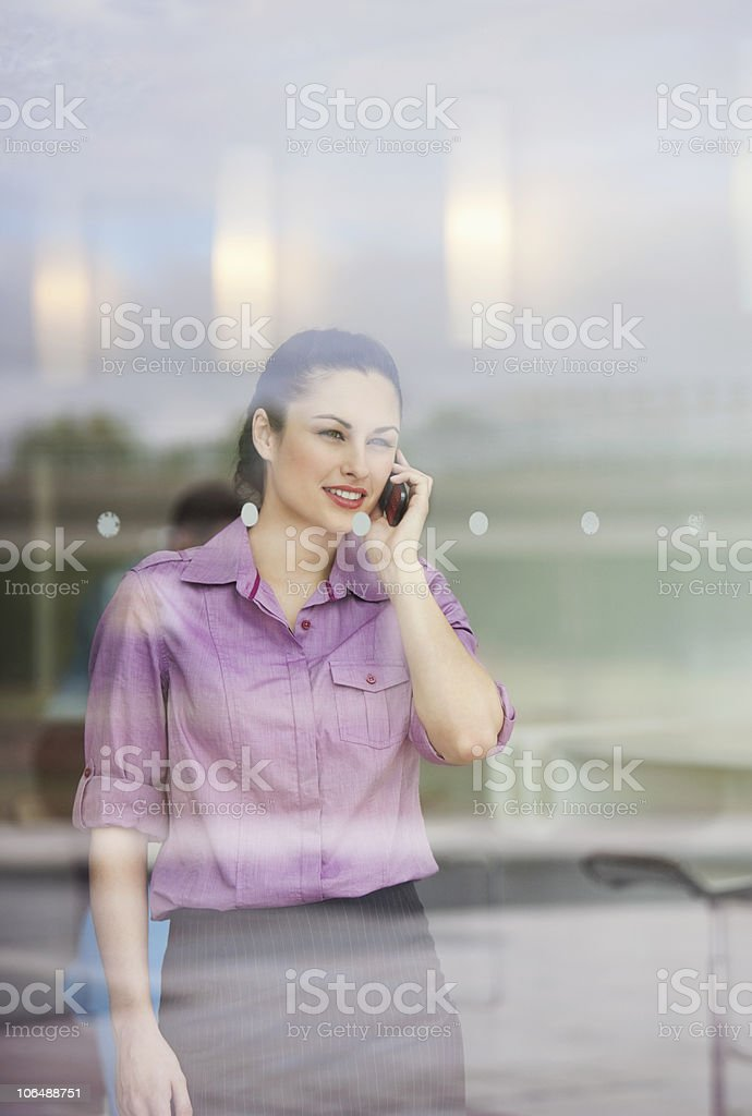 Businesswoman using cell phone behind glass window royalty-free stock photo