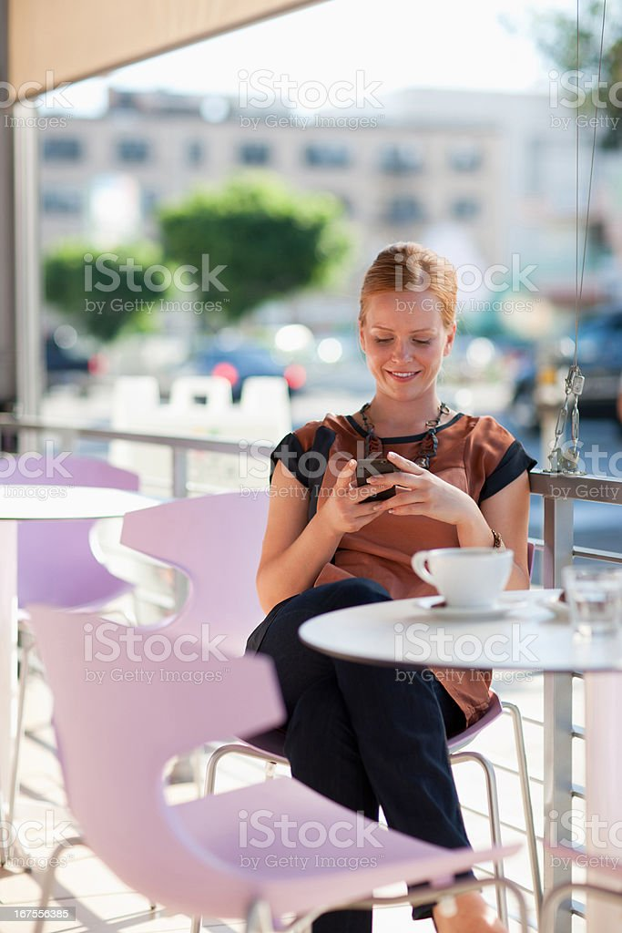 Businesswoman using cell phone in cafe stock photo