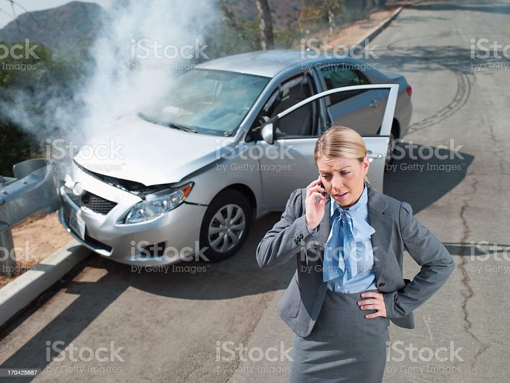 Businesswoman using cell phone near car wrecked on guardrail stock photo