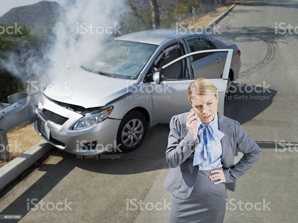 Businesswoman using cell phone near car wrecked on guardrail royalty-free stock photo