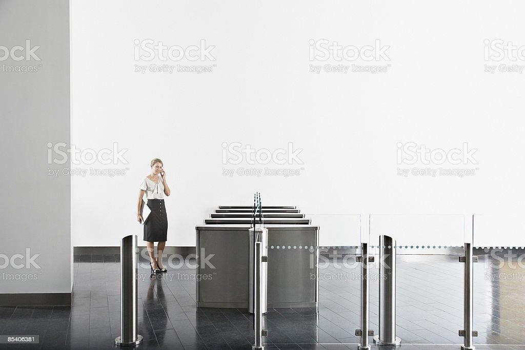 Businesswoman using cell phone near turnstile stock photo