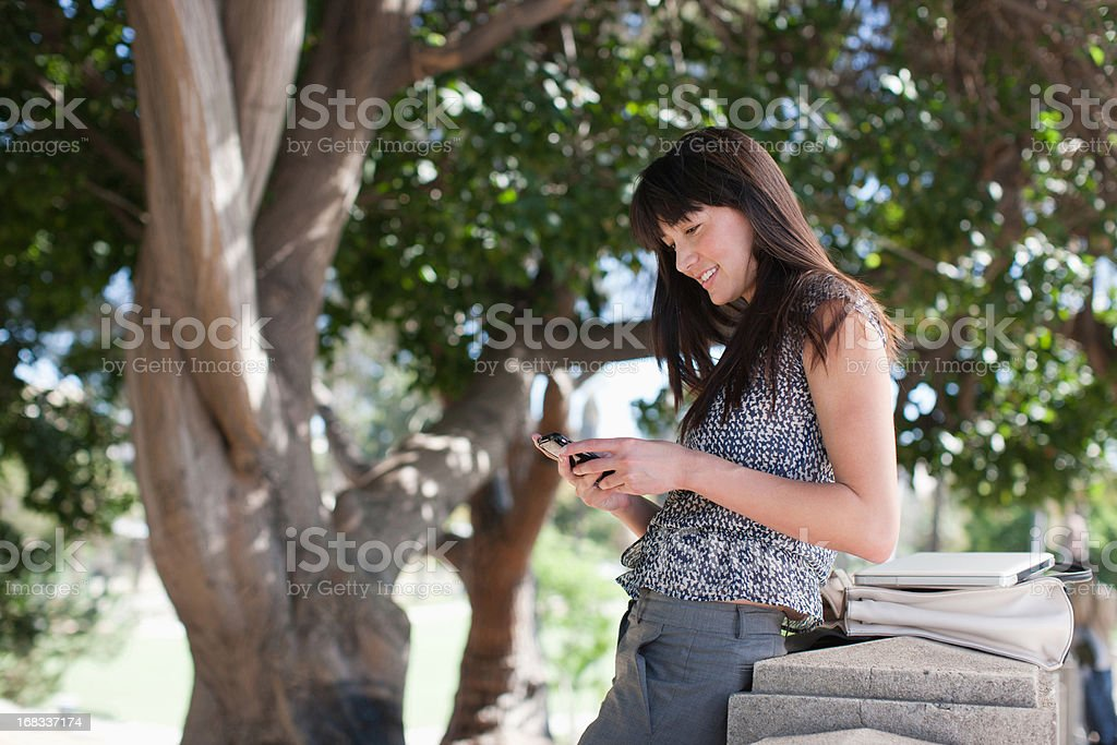 Businesswoman using cell phone outdoors royalty-free stock photo
