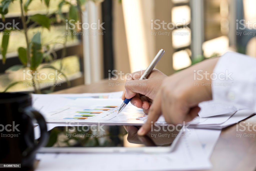 Businesswoman using digital tablet and checking financial report stock photo