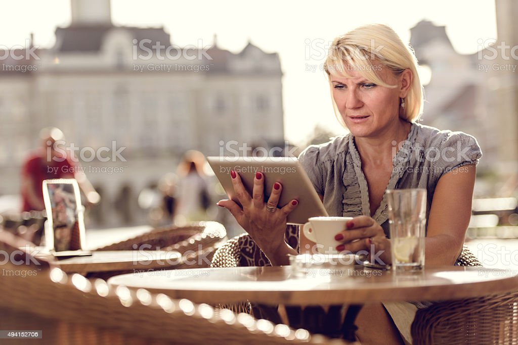 Businesswoman using digital tablet in a city cafe. stock photo