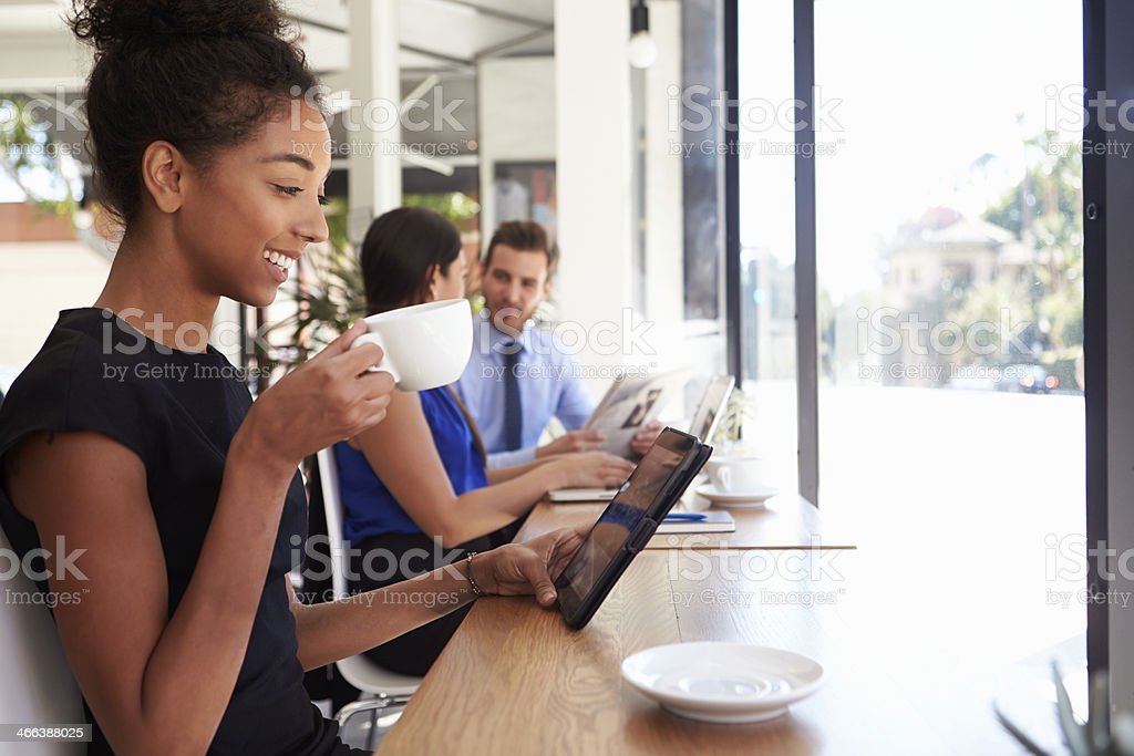 Businesswoman Using Digital Tablet In Coffee Shop stock photo