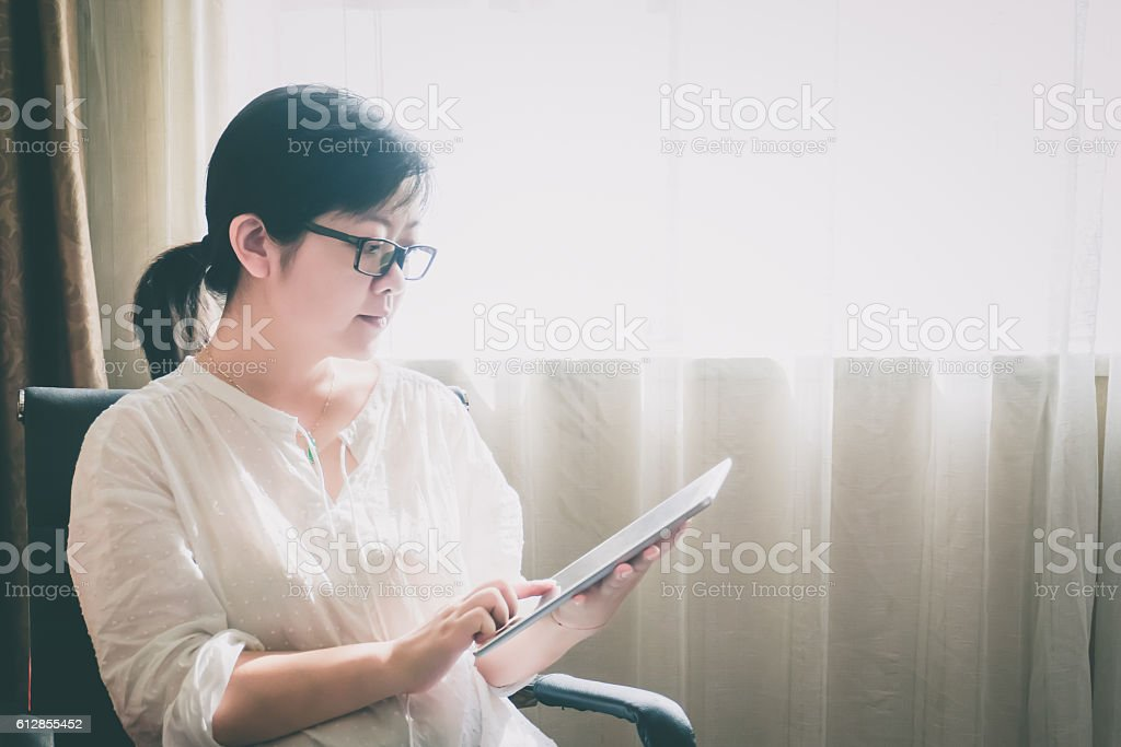 Businesswoman using digital tablet indoors stock photo