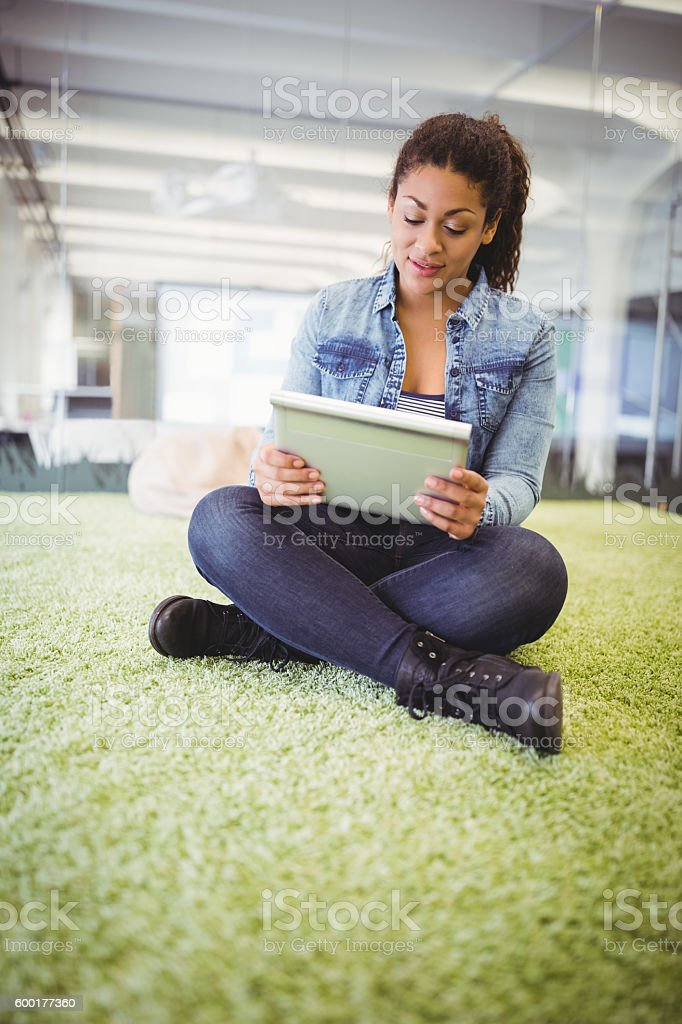 Businesswoman using digital tablet while sitting on stock photo