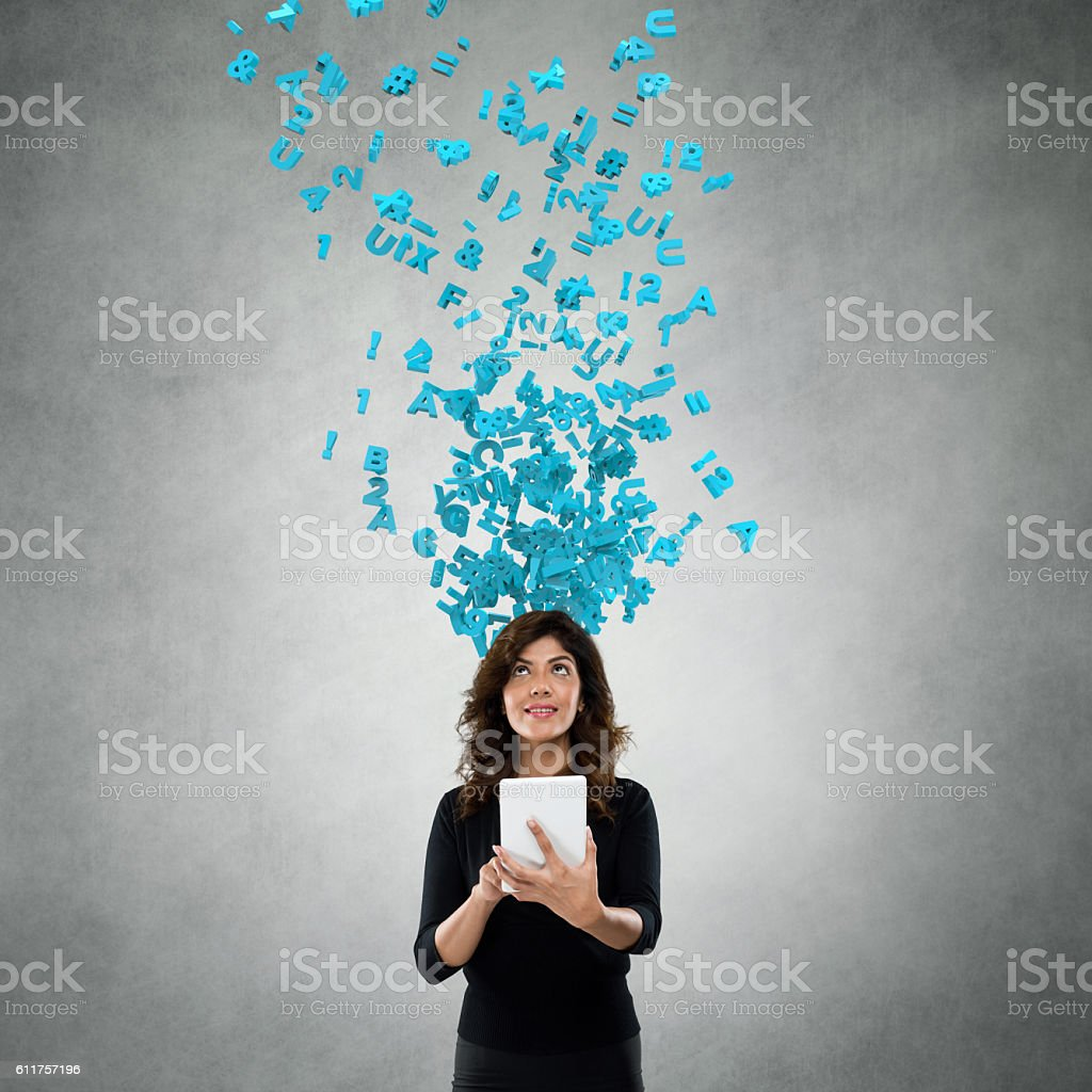 Businesswoman using digital tablet with flying alphabets stock photo