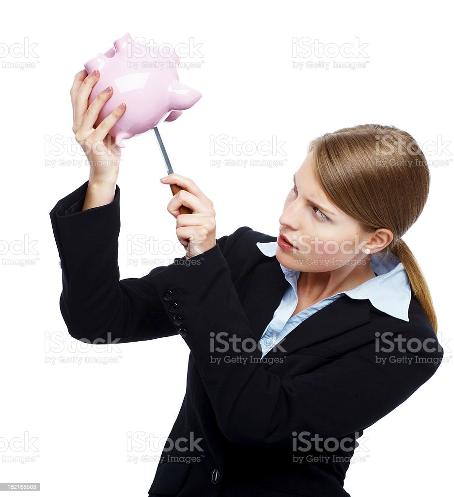 Businesswoman using knife to remove money from a piggybank royalty-free stock photo