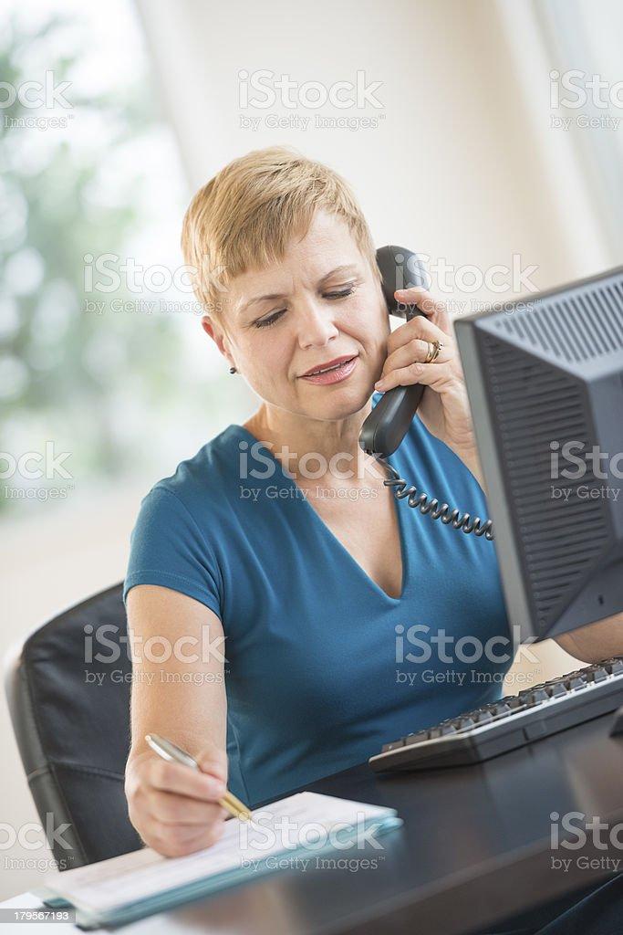Businesswoman Using Landline Phone While Working At Desk royalty-free stock photo