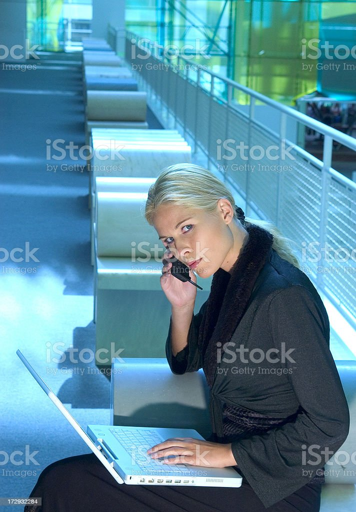 Businesswoman using laptop and on the phone royalty-free stock photo