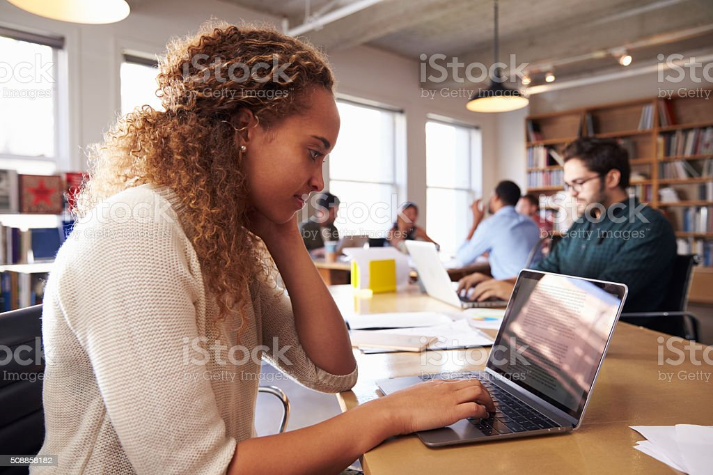 Businesswoman Using Laptop At Desk In Busy Office stock photo