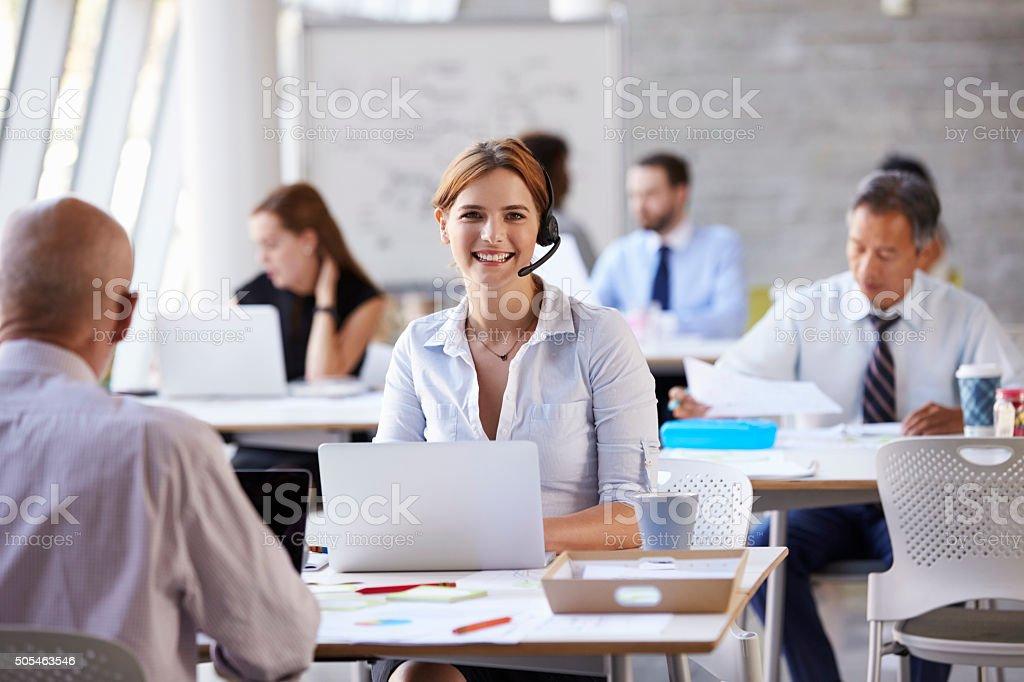 Businesswoman Using Laptop In Customer Service Department stock photo