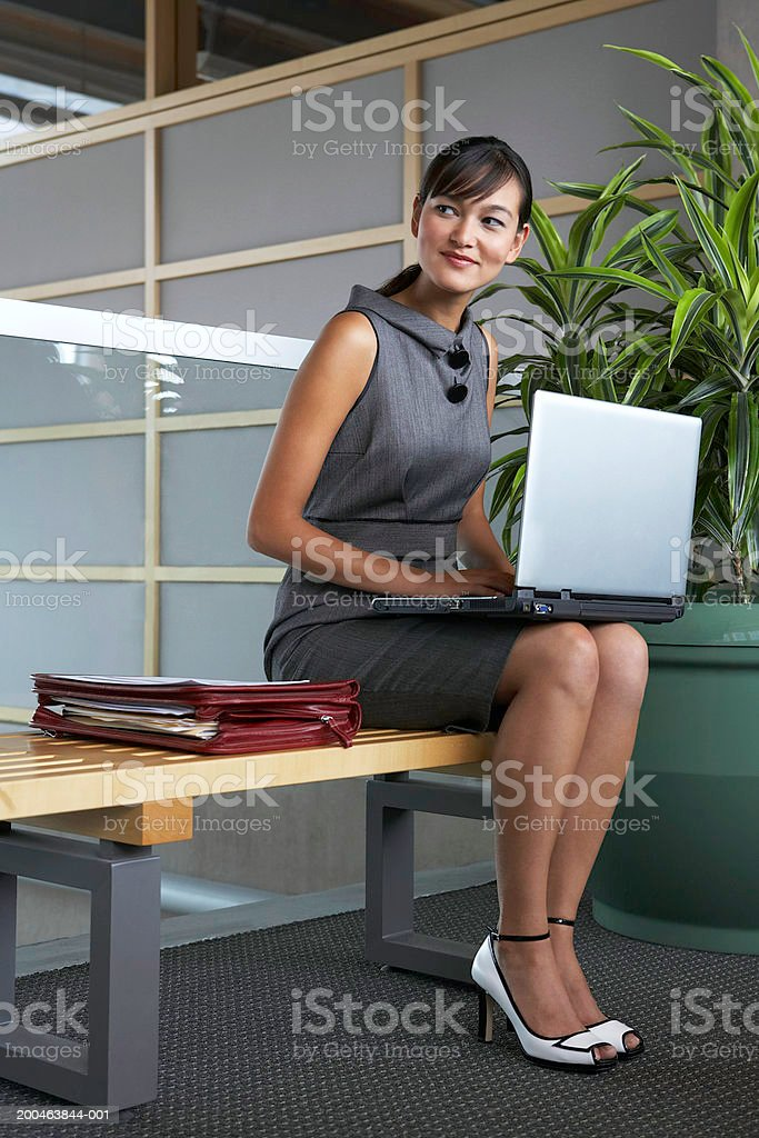 Businesswoman using laptop on bench in lobby, smiling royalty-free stock photo