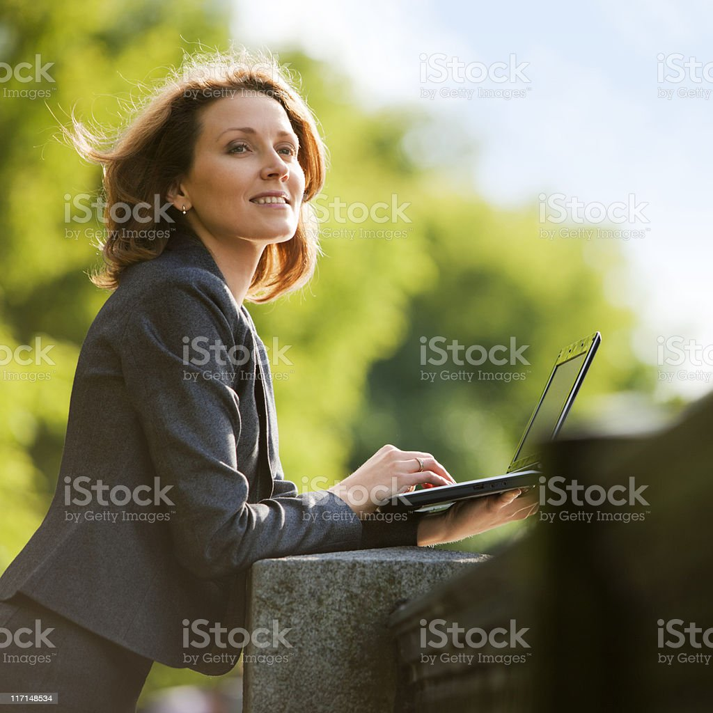 Businesswoman using laptop outdoors and smiling royalty-free stock photo