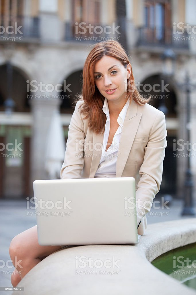Businesswoman using laptop outdoors royalty-free stock photo
