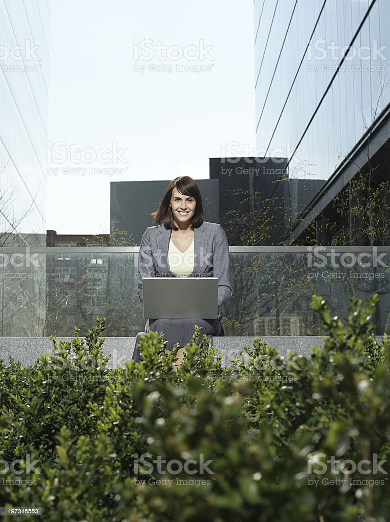 Businesswoman Using Laptop Outside Buildings stock photo