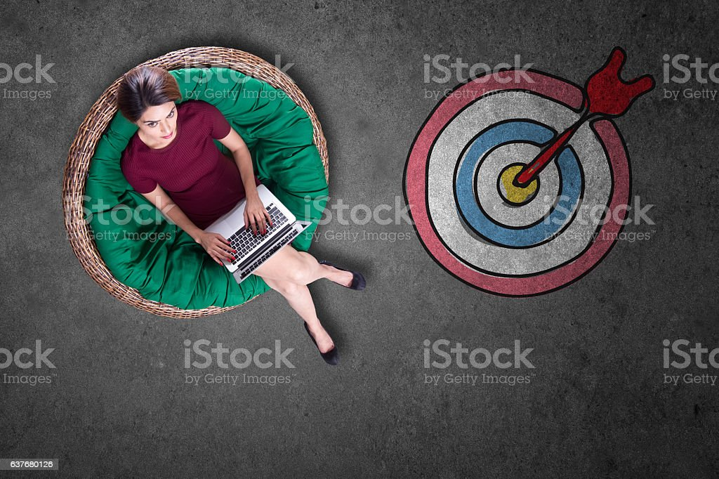 Businesswoman using laptop with bull's eye stock photo