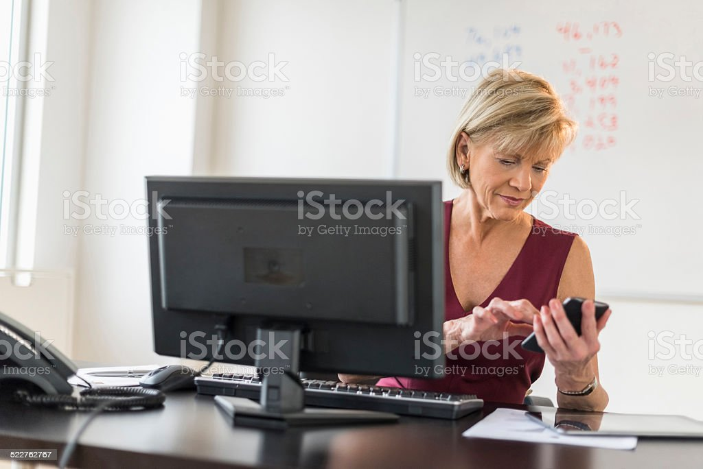 Businesswoman Using Mobile Phone At Computer Desk stock photo
