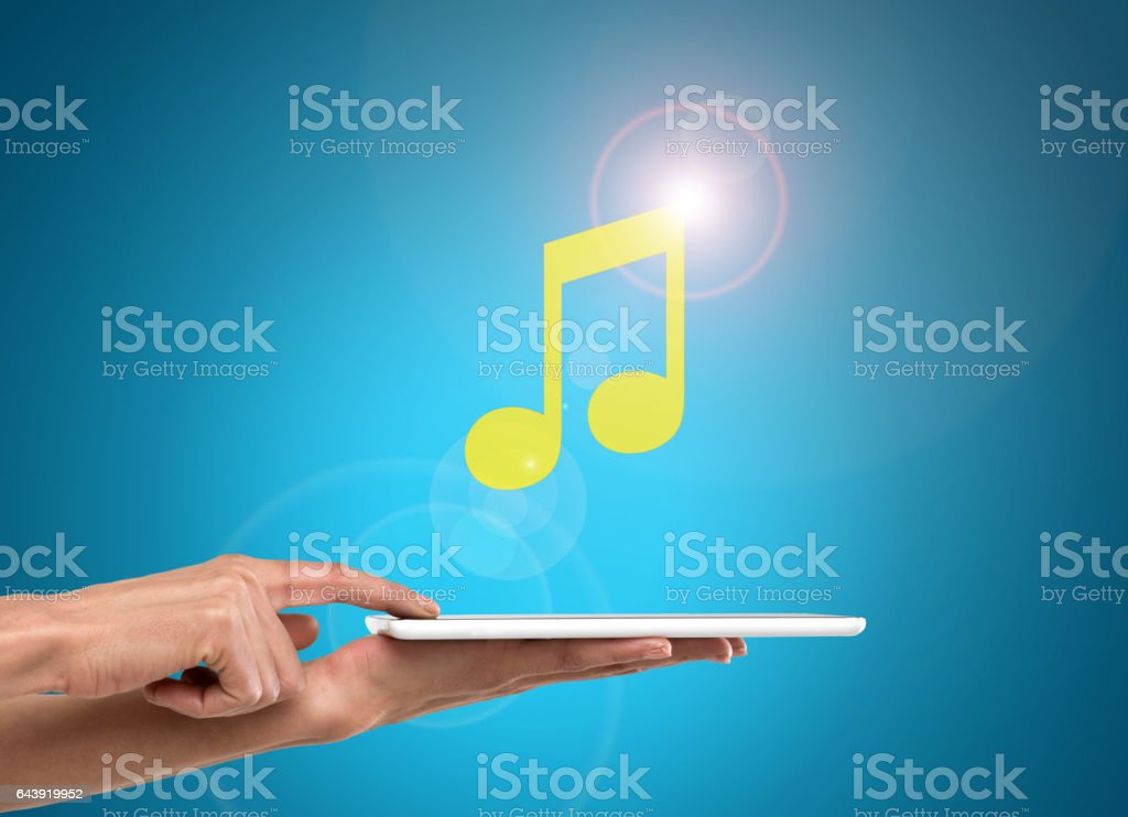 Businesswoman using musical note icon on digital tablet stock photo