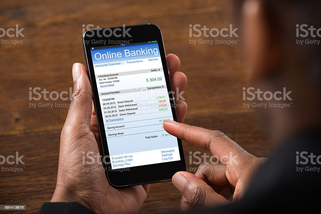 Close-up Of Young Businesswoman Using Online Banking On Mobile Phone...