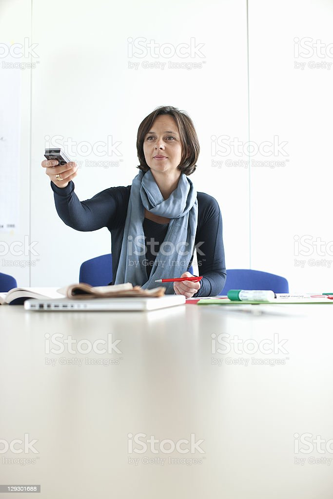Businesswoman using remote in office royalty-free stock photo