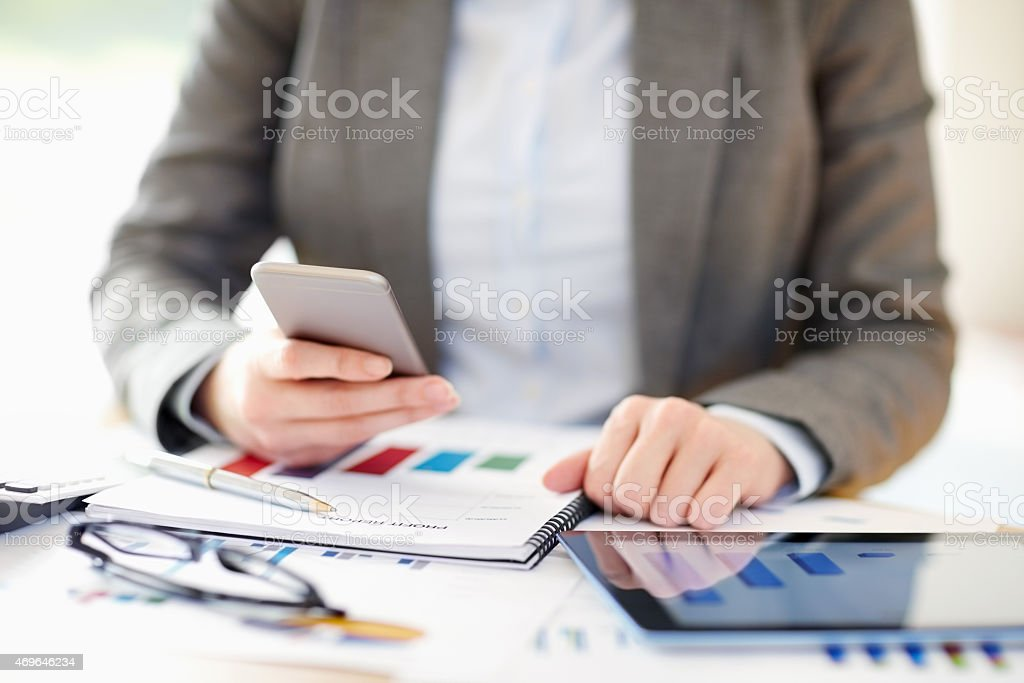 Businesswoman using smart phone while calculating finance stock photo