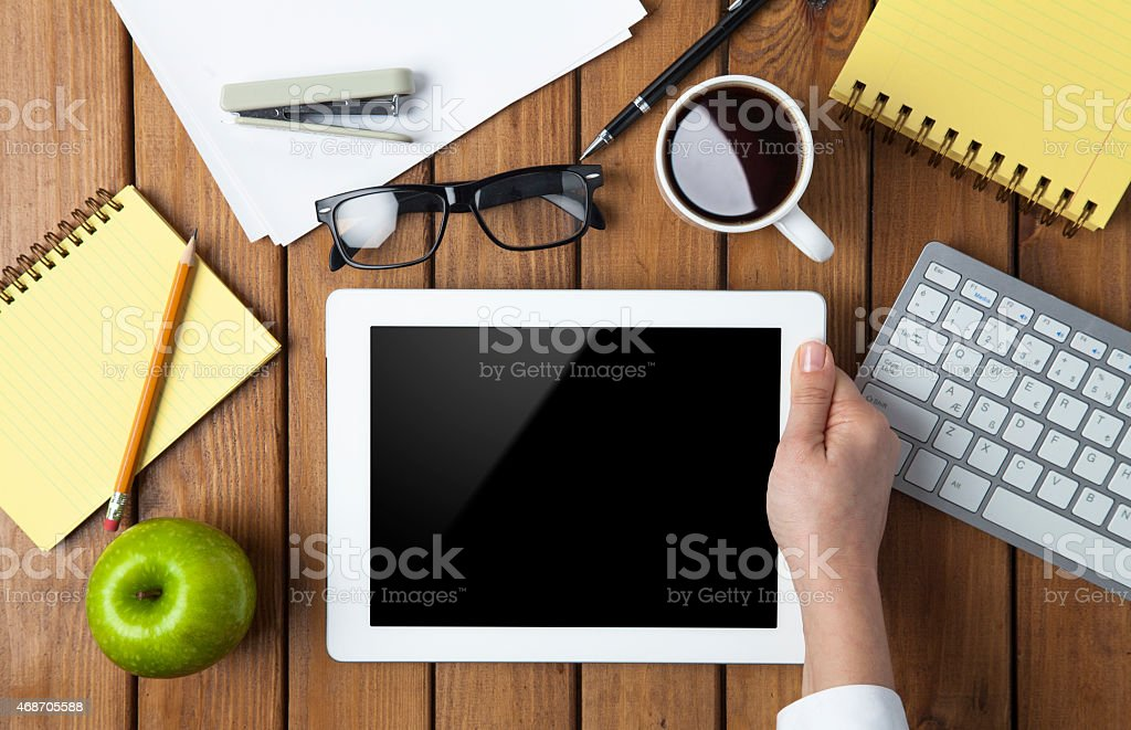 Businesswoman using tablet pc on her office table stock photo