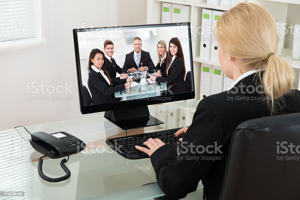 Businesswoman Video Conferencing With Colleagues On Computer stock photo