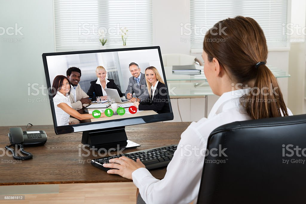 Businesswoman Videochatting With Colleagues On Computer stock photo