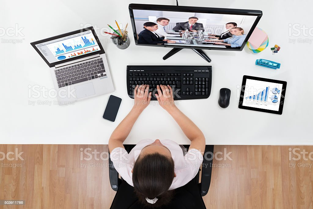 Businesswoman Videoconferencing With Co-workers On Computers stock photo
