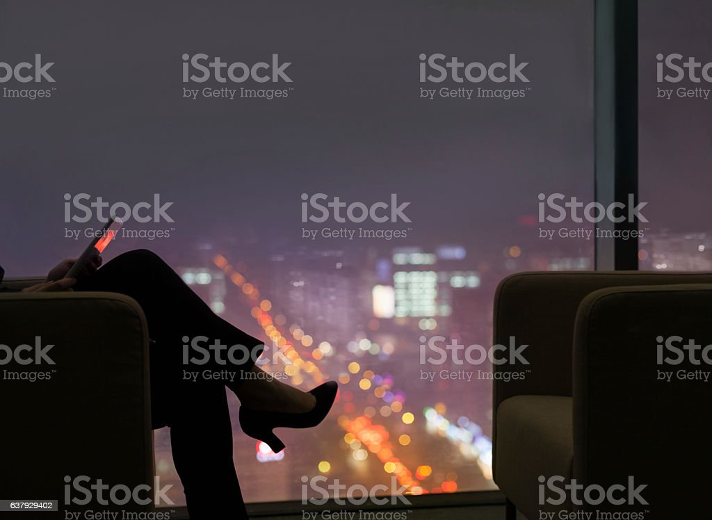 Businesswoman viewing tablet computer in office at night stock photo