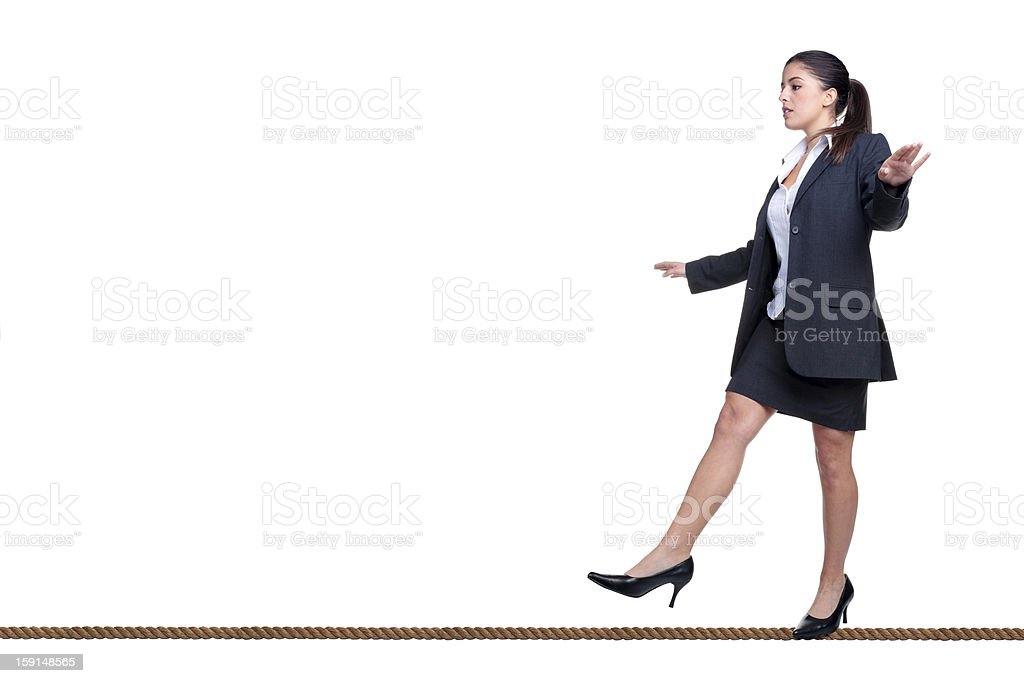 Businesswoman walking a tightrope isolated on white. stock photo