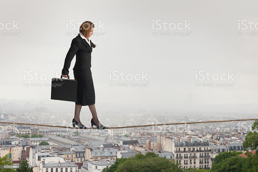 businesswoman walking a tightrope stock photo