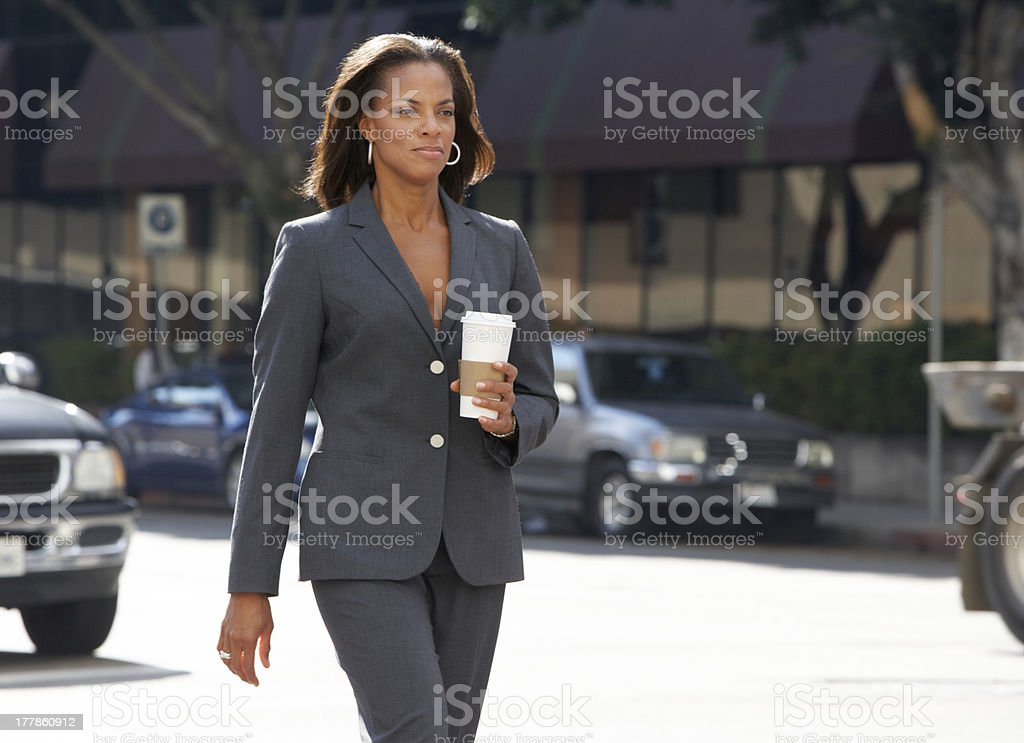 Businesswoman Walking Along Street Holding Takeaway Coffee royalty-free stock photo