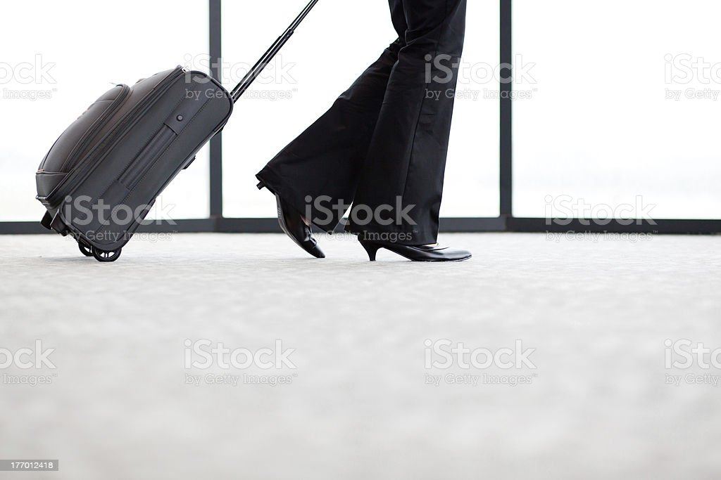 businesswoman walking in airport with luggage royalty-free stock photo