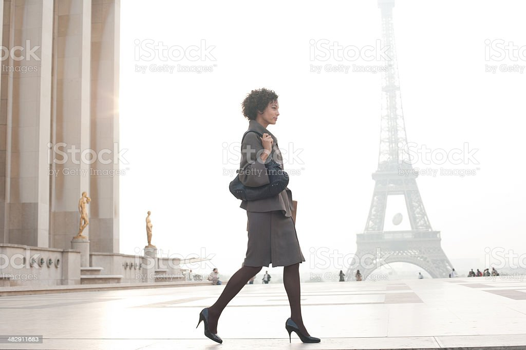 Businesswoman walking in plaza by Eiffel Tower stock photo