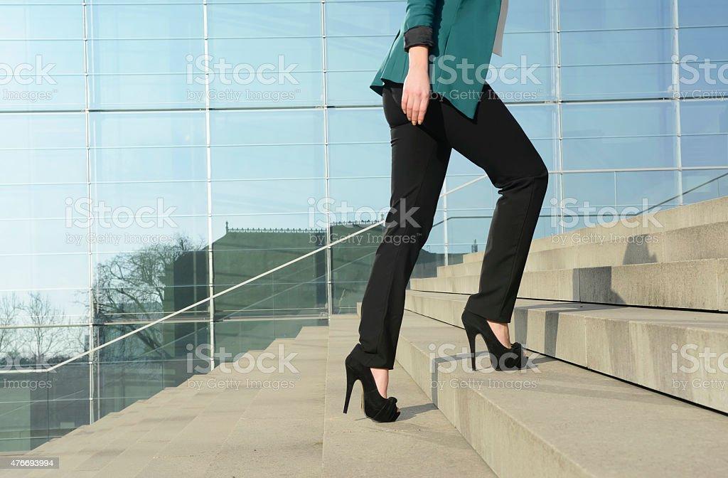 Businesswoman walking on stairs stock photo