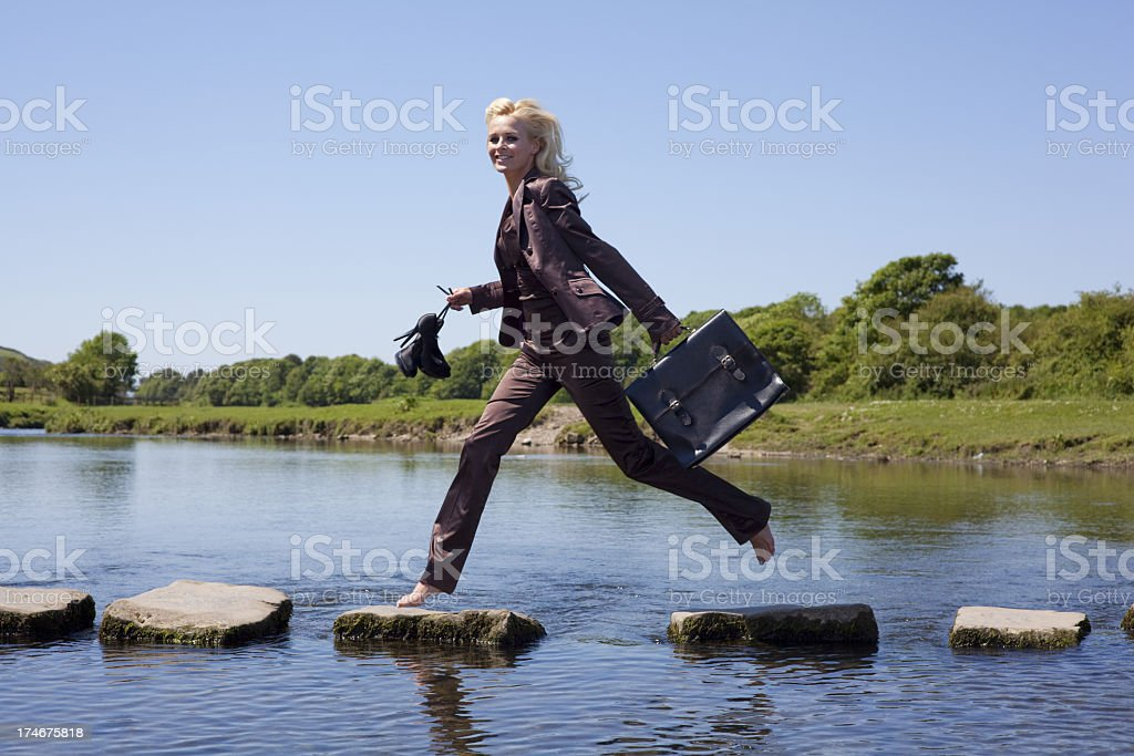 A businesswoman walking on the stepping stones successfully  stock photo