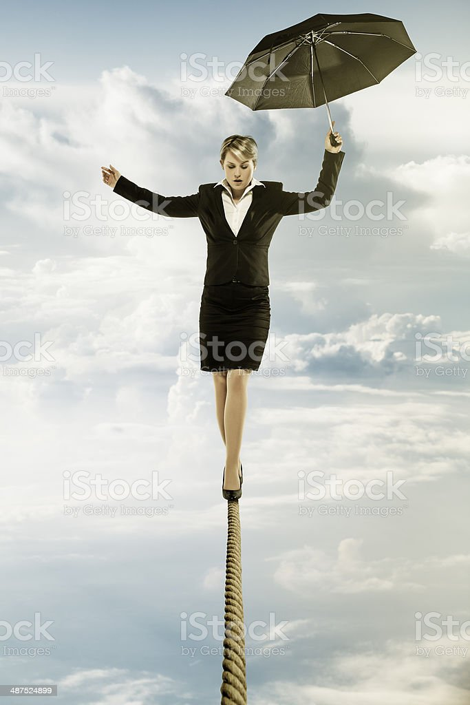 Businesswoman walking on tightrope stock photo