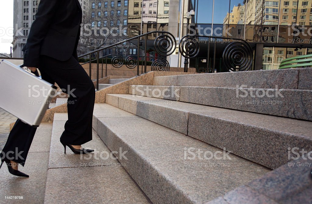 Businesswoman walking up stairs in black heels stock photo