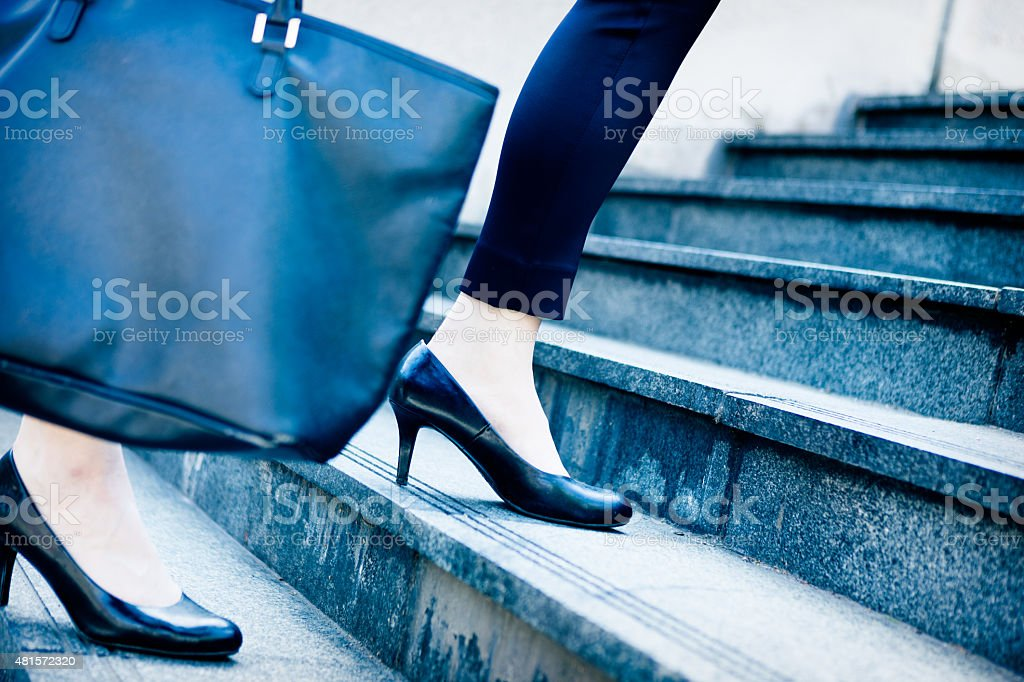 Businesswoman walking up stairs to higher level stock photo
