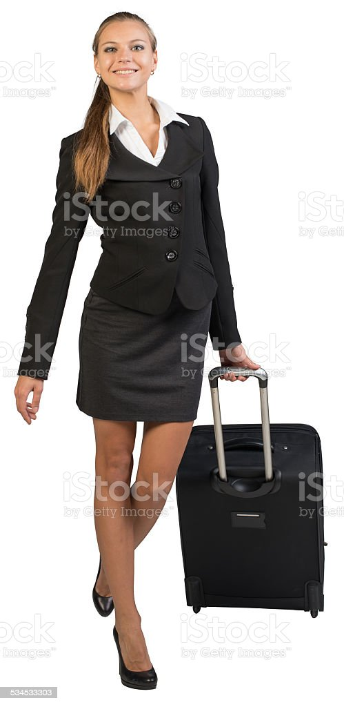 Businesswoman walking with wheeled suitcase, looking at camera, smiling stock photo