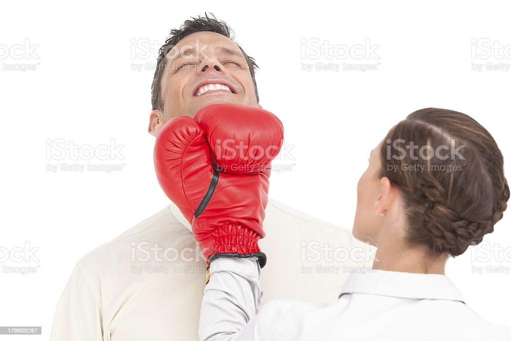 Businesswoman wearing boxing gloves punching businessman royalty-free stock photo