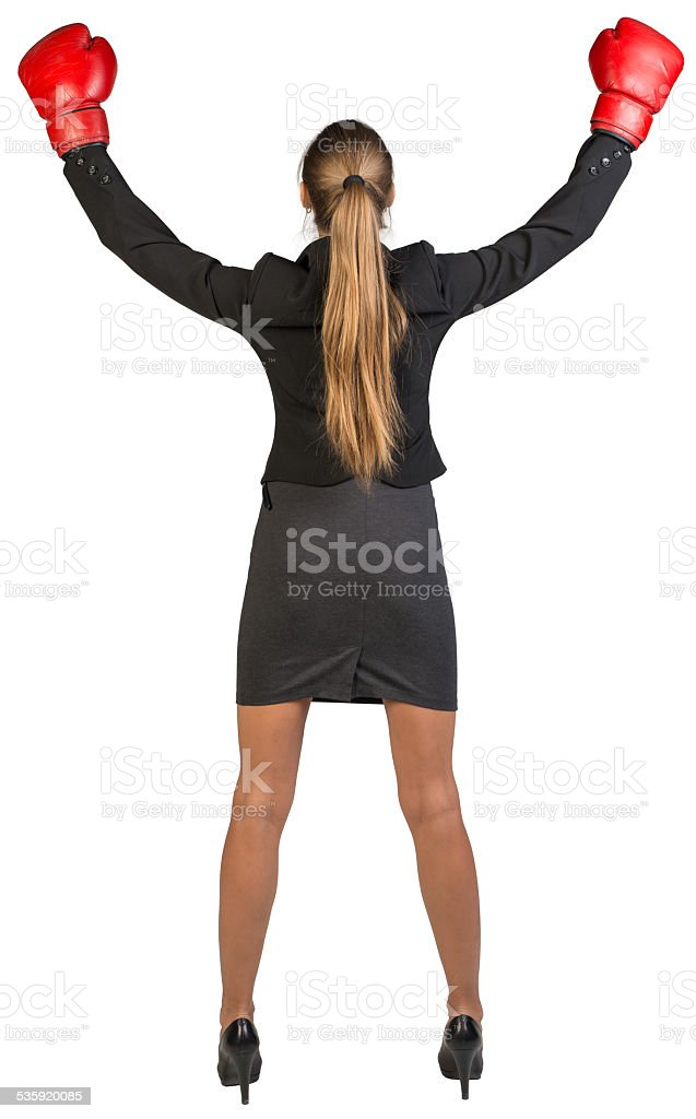 Businesswoman wearing boxing gloves wins. Rear view stock photo