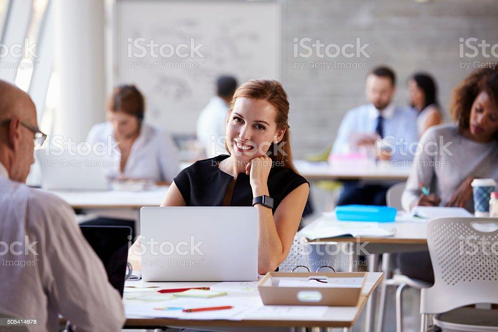 Businesswoman Wearing Smart Watch In Busy Office stock photo