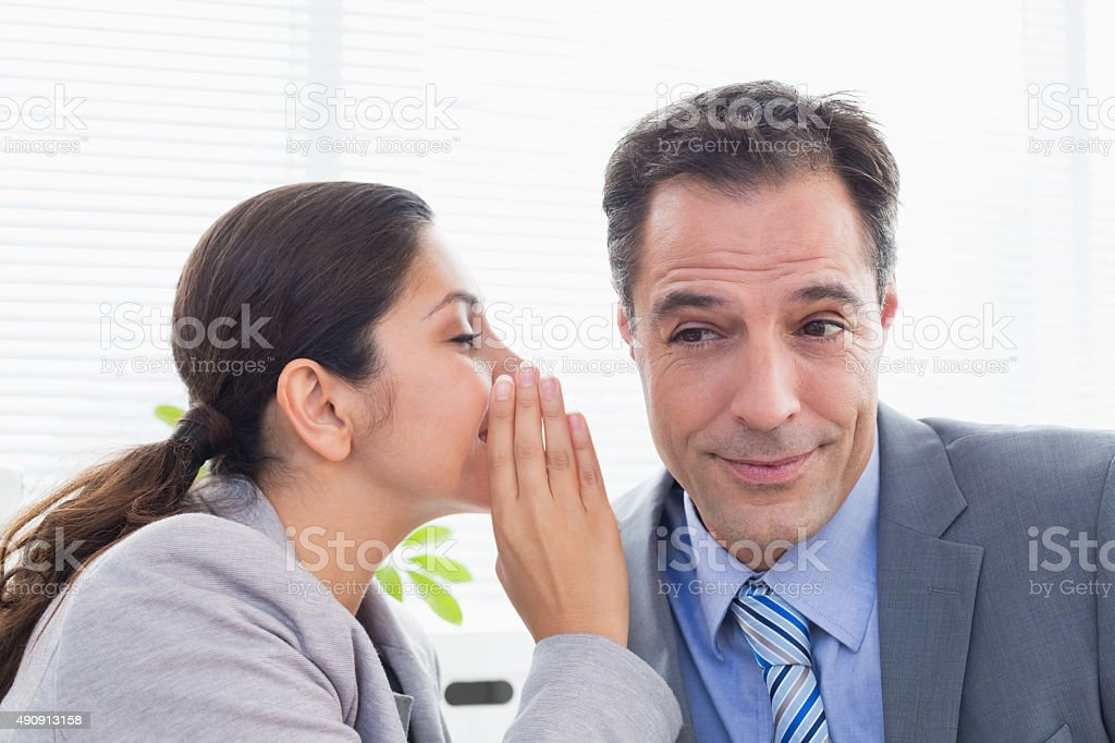 Businesswoman whispering something to her colleague stock photo