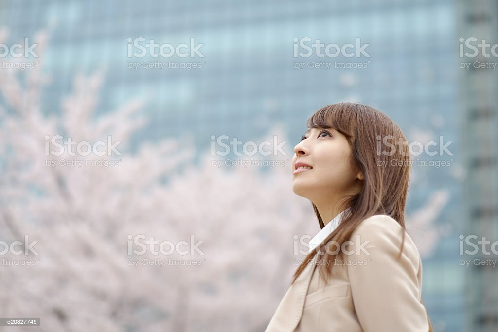 businesswoman who is relaxed in front of a cherry tree stock photo