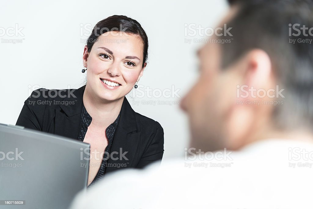 A businesswoman with a client looking at a laptop royalty-free stock photo